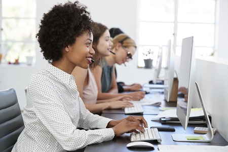 Young black woman working at computer in office with headset Stock Photo