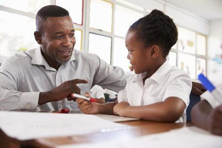 Teacher helping elementary school girl at her desk, close up Banco de Imagens