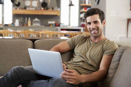Portrait Of Man Sitting On Lounge Sofa Using Laptop