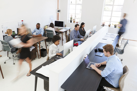 Young colleagues at computers in a busy open plan office Stock Photo