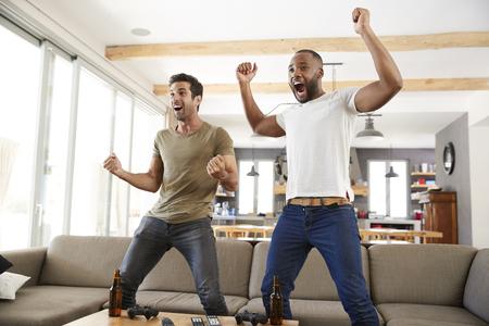 Twee opgewonden mannelijke vrienden vieren het kijken naar sport op televisie Stockfoto