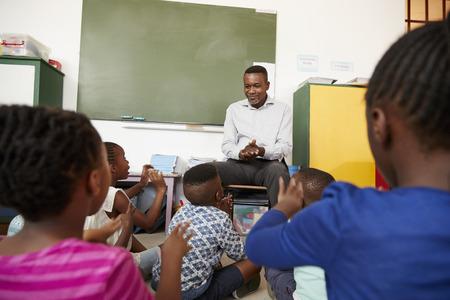 Niños de primaria sentados en el piso escuchando a un maestro Foto de archivo - 85280449