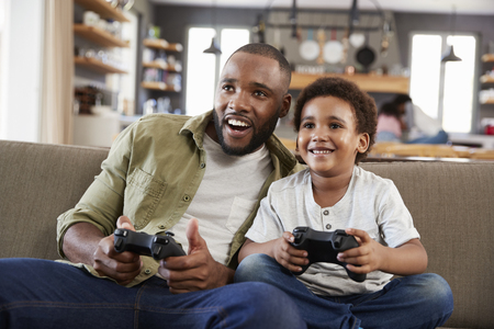 Father And Son Sitting On Sofa In Lounge Playing Video Game Stok Fotoğraf - 85280450