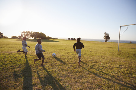 Three elementary school kids playing football in a field