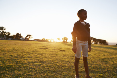 African elementary school girl standing in a park at sunset