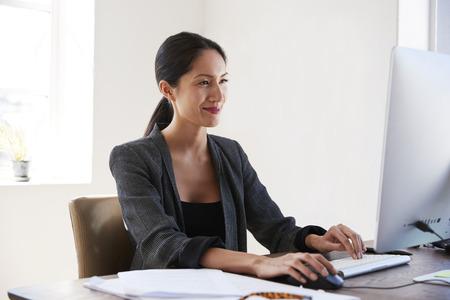 Jonge Aziatische vrouw die computer met behulp van, die in een bureau glimlacht