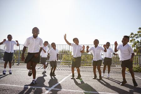 Enfants de l'école élémentaire s'amuser dans la cour de récréation Banque d'images - 85280460
