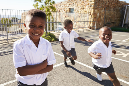 Young African schoolboys running in school playground