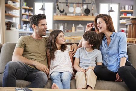 ラウンジでソファーに座っている幸せな家族一緒に話す