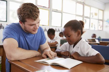 Vrijwilligers leraar helpen schoolmeisje bij haar bureau, close-up Stockfoto