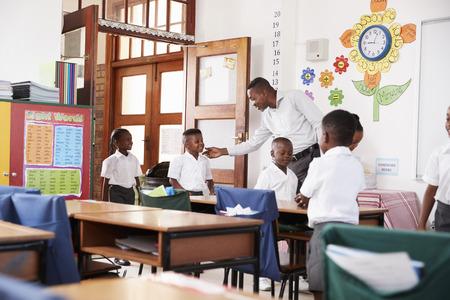 Teacher greets kids arriving at elementary school classroom