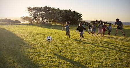 교사와 초등학생들은 축구 경기를 필드에서합니다.