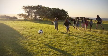 Teacher and elementary school kids play football in a field Stock Photo