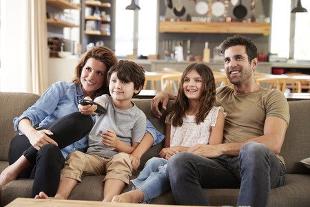 Family Sitting On Sofa In Open Plan Lounge Watching Television Standard-Bild