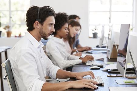 사무실에서 컴퓨터에서 작업에 헤드셋과 히스패닉 남자