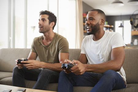 비디오 게임을 재생하는 라운지에서 소파에 앉아 두 남성 친구 스톡 콘텐츠
