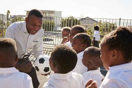 教師のボールを持つ学校の遊び場の若い子供たち