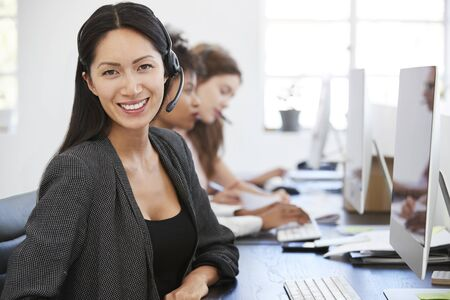Young Asian woman with headset smiling to camera in office