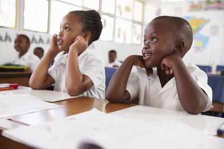 Dos niños escuchando durante una lección en una escuela primaria Foto de archivo - 85280519