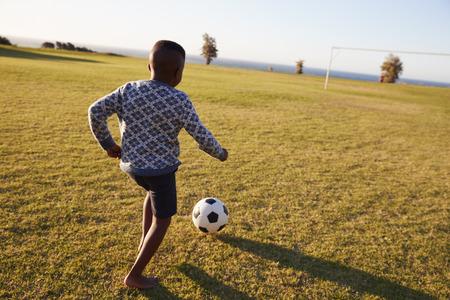 Elementary school boy playing football in an open field