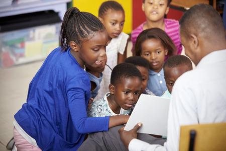 Teacher showing kids a book during elementary school lesson Stok Fotoğraf