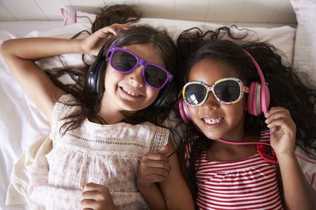 선글라스를 착용 하 고 음악을 듣고 두 여자의 초상화 스톡 콘텐츠