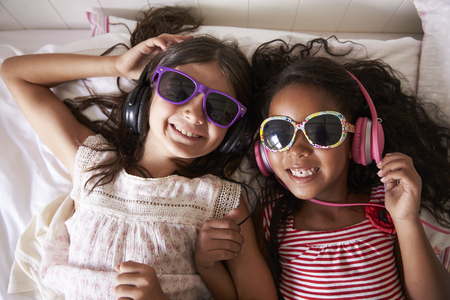 Porträt von zwei Mädchen, die Sonnenbrille tragen und Musik hören Standard-Bild - 85280723