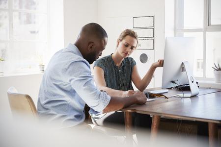 Man en vrouw die documenten bespreken bij haar bureau in een bureau