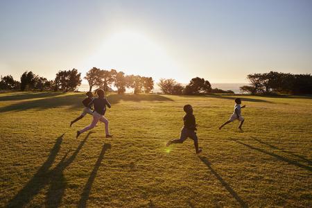 Cuatro niños de escuela primaria que se ejecutan en un campo abierto Foto de archivo - 85280742