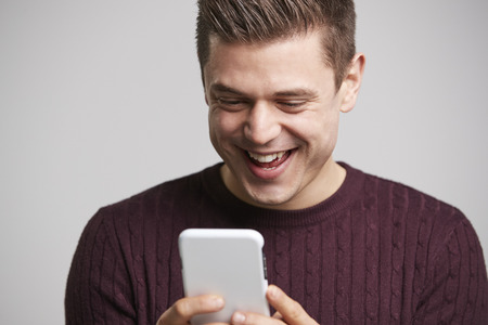 Close up portrait of a young white man using a smartphone Stok Fotoğraf