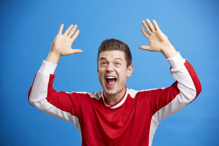 Young white male sports fan celebrating with arms in the air Stock Photo