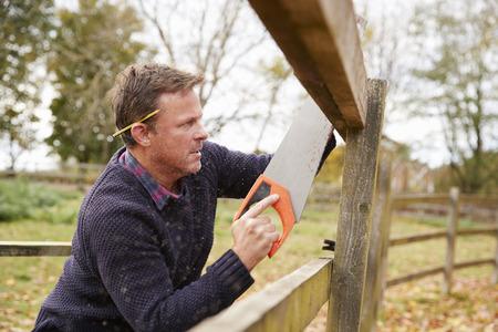 屋外フェンスを固定する中年の男性を見た 写真素材 - 85441127
