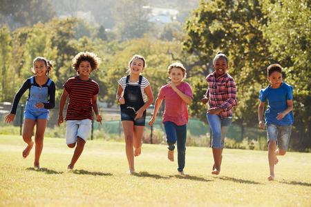 公園で走っている6人の前の十代の友人、正面図、クローズアップ 写真素材