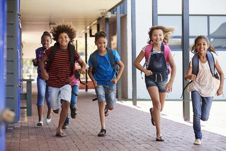 School kids running in elementary school hallway, front view