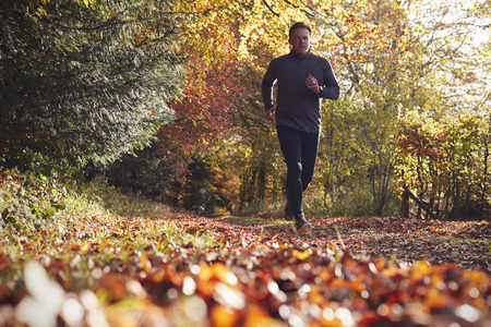가을 숲을 통해 실행 성숙한 남자의 낮은 각도보기
