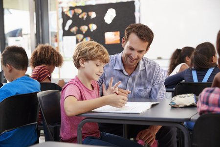 Teacher and young school boy looking at notebook in class Imagens