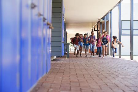 跑到照相机的学校孩子在小学走廊里