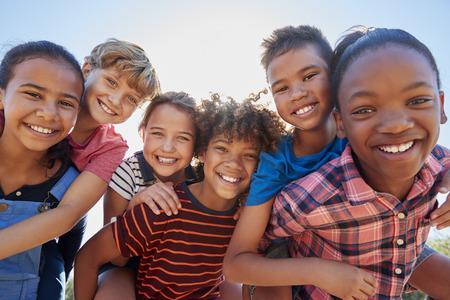 Sechs jugendliche Freunde, die in einem Park, nahes hohes Porträt huckepack tragen Standard-Bild - 85441739