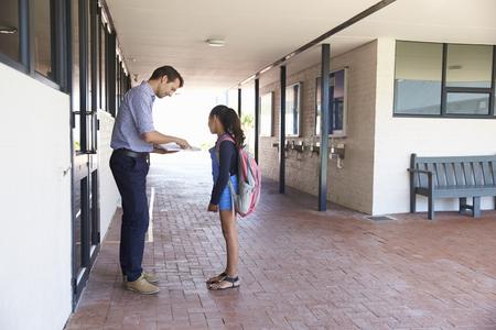 학교 교사 교실 밖에서 여학생에게 책을 보여주는 스톡 콘텐츠