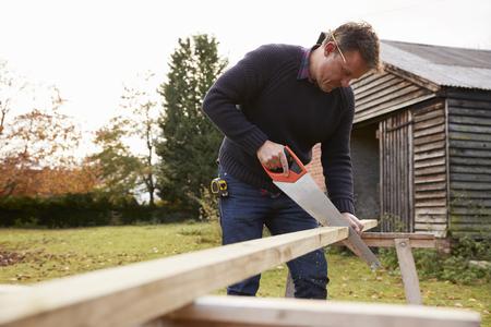 Mature Man Sawing Wood Outdoors Фото со стока