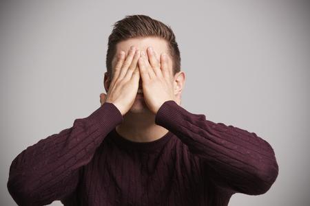Retrato de un joven blanco con las manos cubriéndose la cara Foto de archivo - 85441839
