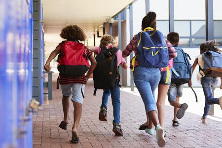 Crianças da escola que correm no corredor da escola primária, vista traseira