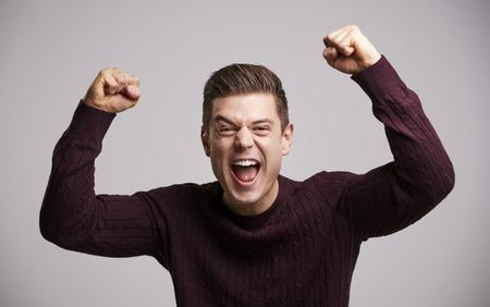 「腕を上げている若い白人男性を祝う肖像画」 写真素材