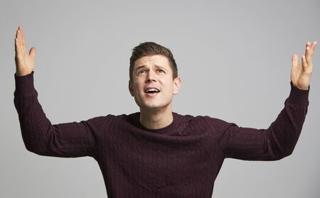 Portrait of a shocked young white man with arms in the air