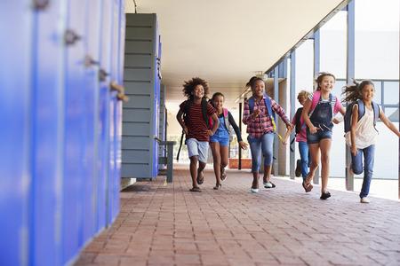 Niños de la escuela corriendo a la cámara en el pasillo de la escuela primaria Foto de archivo - 85457567