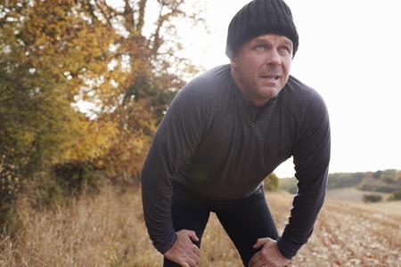 森の中で運動中に息を一時停止する成熟した男性ランナー 写真素材