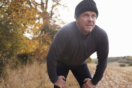 Reifer männlicher Läufer, der für Atem während der Übung im Holz pausiert Standard-Bild