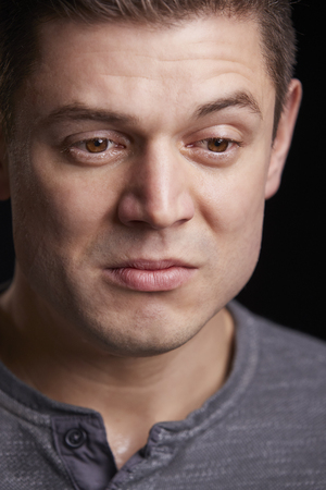Vertical portrait of crying young white man looking down