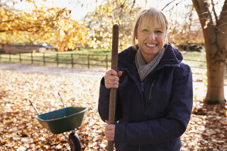 Portrait Of Mature Woman Raking Autumn Leaves In Garden 版權商用圖片