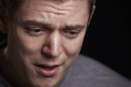 Close up portrait of crying young white man looking down Stok Fotoğraf
